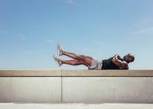 Mannelijke atleet die abdominals maken Stock Fotografie