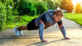Mannelijke atleet die in het park uitoefenen Portret van een mannelijke kerel die opdrukoefeningen doen Het concept een gezonde l Royalty-vrije Stock Afbeeldingen