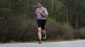 Mannelijke atleet die op weg in hout lopen Langzame Motie stock video