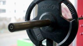 Mannelijke atleet die voor intensieve training, ladende zware platen op barbell voorbereidingen treffen stock footage
