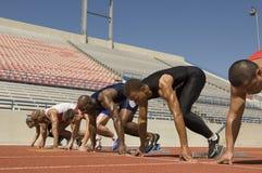 Mannelijke Atleten bij Startblokken stock foto's