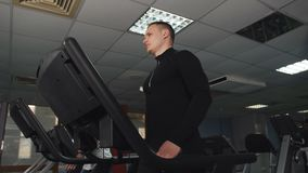Mannelijke atletisch bouwt, werkt in de gymnastiek uit Een mens leidt op een tredmolen op bij de atletische club stock video
