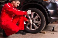 Mannelijke auto mechanische zitting dichtbij een zwarte sedan en het schroeven auto w Royalty-vrije Stock Afbeeldingen