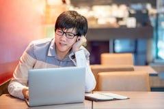 Mannelijke Aziatische zakenman die in de koffie werken royalty-vrije stock foto