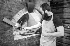 Mannelijke Baker kokende oven voor het koken en bewogen de steenkolen met de pook Royalty-vrije Stock Afbeeldingen