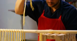 Mannelijke bakker die deegwaren op deegwarenrek 4k schikken stock video