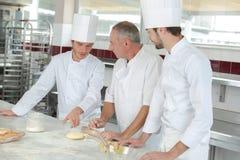 Mannelijke bakker die het gebakje van leerlingengeheimen tonen royalty-vrije stock foto's