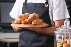 Mannelijke bakker die houten raad met heerlijke croissants in winkel houden royalty-vrije stock afbeeldingen