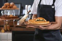 Mannelijke bakker die houten raad met heerlijke pastei binnen houden stock afbeelding