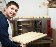Mannelijke bakker met brood dichtbij oven bij supermarkt royalty-vrije stock foto
