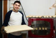 Mannelijke bakker met brood dichtbij oven bij supermarkt royalty-vrije stock fotografie
