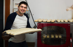 Mannelijke bakker met brood dichtbij oven bij supermarkt stock afbeeldingen