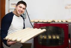Mannelijke bakker met brood dichtbij oven bij supermarkt stock afbeelding