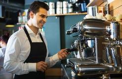 Mannelijke barista die dichtbij koffiemachine glimlachen royalty-vrije stock foto