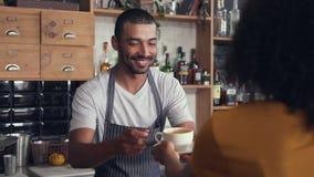 Mannelijke barista dienende koffie aan de klant bij teller stock footage