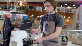 Mannelijke barista kookt koffie in een cafetaria, drukt grondkoffie en zet in koffiemachine stock video