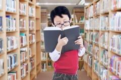Mannelijke basisschoolstudent in bibliotheek Stock Foto's