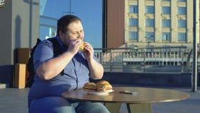 Mannelijke beambte die hamburger voor lunch eten in openlucht, de zwaarlijvigheid van de ongezonde kostvoeding stock videobeelden