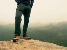 Mannelijke benen in donkere wandelingsbroeken en de schoenen van de leertrekking op piek van rots boven nevelige vallei Overzicht Stock Afbeeldingen