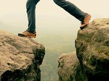 Mannelijke benen in donkere wandelingsbroeken en de schoenen van de leertrekking op piek van rots boven nevelige vallei Overzicht Royalty-vrije Stock Foto's