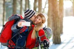 Mannelijke bergbeklimmer die zijn meisje kussen terwijl het maken selfie op w Royalty-vrije Stock Afbeeldingen