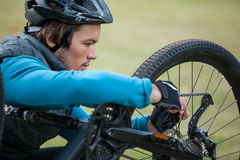 Mannelijke bergfietser die zijn fietsketting bevestigen royalty-vrije stock afbeelding