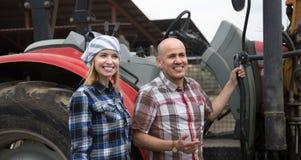Mannelijke bestuurder en medewerker die bij landbouwmachines bij boerenerf werken royalty-vrije stock foto