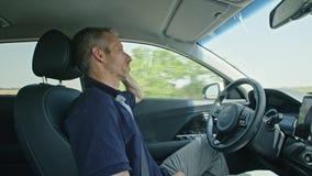 Mannelijke bestuurderszitting in een autonome auto, die de auto laten alleen drijven stock video