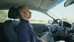 Mannelijke bestuurderszitting in een autonome auto, die de auto laten alleen drijven stock videobeelden