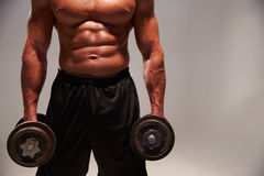 Mannelijke bodybuilder die met zware domoren, met exemplaarruimte uitwerken stock foto's