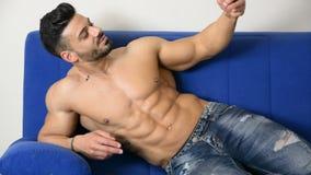 Mannelijke bodybuilder die selfie foto op bank nemen stock video