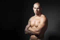 Mannelijke bodybuilder met gevouwen die wapens op grijze achtergrond wordt geïsoleerd Stock Fotografie