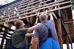 Mannelijke bouwarbeiders die de bouwplannen over onvolledig blokhuis bespreken Stock Fotografie