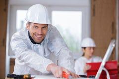 Mannelijke bouwer die kunstmes gebruiken om materialen te snijden stock foto's