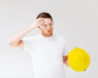 Mannelijke bouwer in veiligheidsbril die helm opstijgen Royalty-vrije Stock Foto's