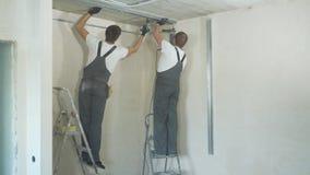 Mannelijke bouwers die elektrische boor het assembleren metaaldrywall profielen op bouwwerf binnen gebruiken stock videobeelden