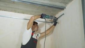 Mannelijke bouwers die elektrische boor het assembleren metaaldrywall profielen op bouwwerf binnen gebruiken stock footage
