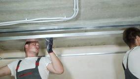Mannelijke bouwers die metaaldrywall profielen op bouwwerf binnen assembleren stock video