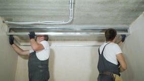 Mannelijke bouwers die metaaldrywall profielen op bouwwerf binnen assembleren stock videobeelden