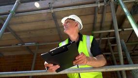 Mannelijke bouwersvoorman, arbeider of architect die aan bouwbouwterrein werken die zich op steiger bevinden die een bouwvakker d stock videobeelden