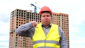 Mannelijke bouwersvoorman, arbeider of architect op bouwbouwterrein die duim tonen beneden en aan camera kijken stock footage