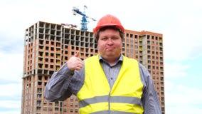 Mannelijke bouwersvoorman, arbeider of architect op bouwbouwterrein die duim tonen en aan camera kijken stock videobeelden