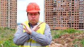 Mannelijke bouwersvoorman, arbeider of architect op bouwbouwterrein die handgebaar tonen die kruisend zijn wapens ophouden stock videobeelden