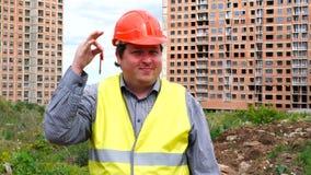 Mannelijke bouwersvoorman, arbeider of architect op bouwbouwterrein die nieuwe huissleutel tonen terwijl het glimlachen aan camer stock videobeelden