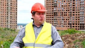 Mannelijke bouwersvoorman, arbeider of architect op bouwbouwterrein die over iets spreken stock footage