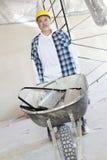 Mannelijke bouwvakker die zich met een kruiwagen bevinden Stock Foto's