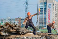 Mannelijke bouwvakkers die bij een bouwwerf werken stock afbeeldingen
