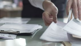 Mannelijke bureaumanager die documenten controleren op lijst en financieel verslag vullen stock footage