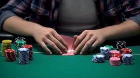 Mannelijke casinospeler die zijn kaartcombinatie in de toernooien van het pookspel controleren stock foto's