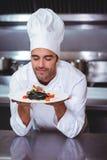 Mannelijke chef-kok met ogen gesloten ruikend voedsel royalty-vrije stock afbeeldingen